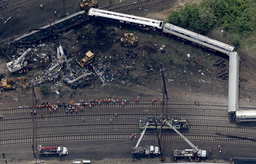 Investigators and first responders work near the wreckage of Amtrak 188 in May 2015. Eight people died; over 200 were injured.
