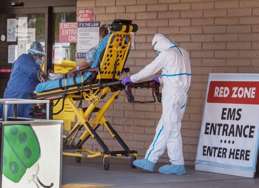 A patient is taken from an ambulance to the emergency room of a hospital in the Navajo Nation town of Tuba City, Ariz., on May 24. Weeks of delays in delivering vital coronavirus aid to Native American tribes exacerbated the outbreak, according to Navajo Nation President Jonathan Nez.