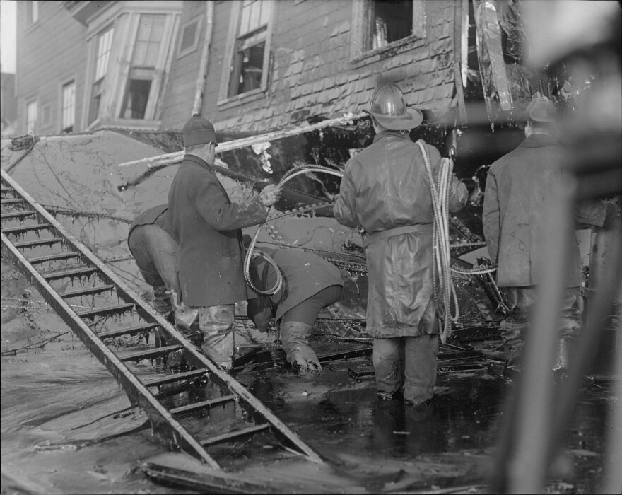 Firemen stand in thick molasses after the disaster in 1919. The Great Molasses Flood in Boston's North End killed 21 people and injured 150.