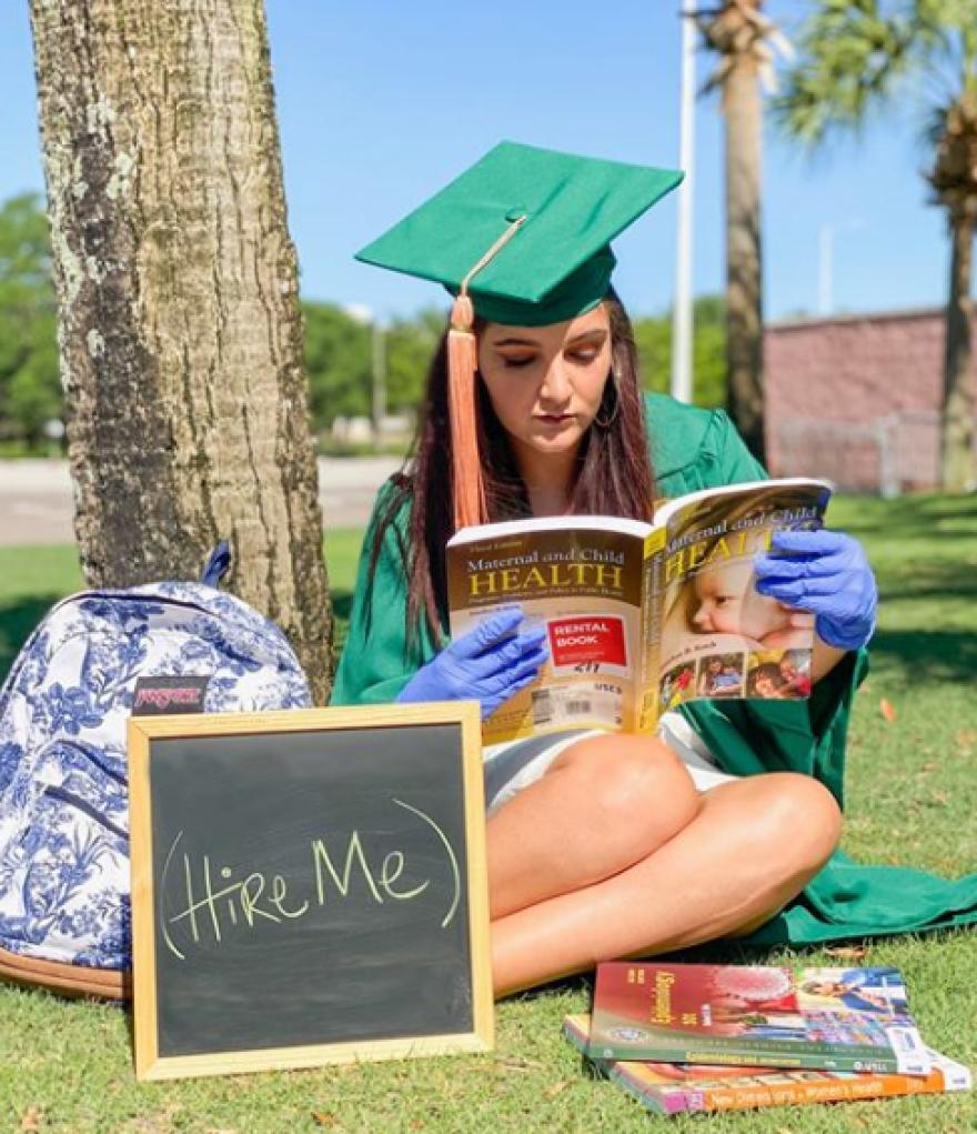 "A young woman in cap and gown sits by a sign that says ""hire me."""