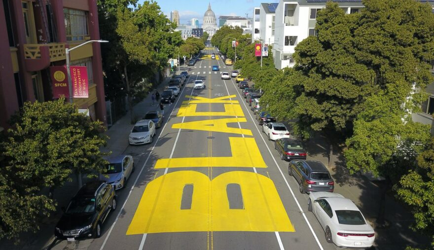 """An aerial photo shows a giant street mural reading """"Black Lives Matter"""" spanning three city blocks near City Hall in San Francisco, California."""