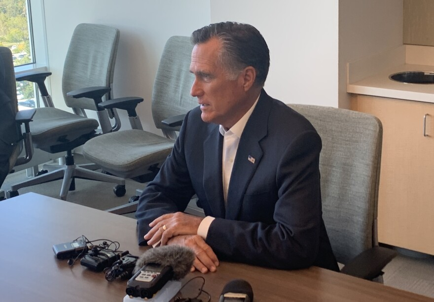 A man sitting at a table speaking into microphones.