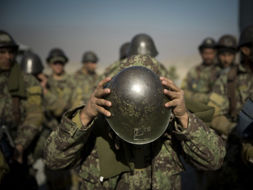 An Afghan army soldier adjusts his helmet as he lines up with others at a training facility in the outskirts of Kabul in 2013.