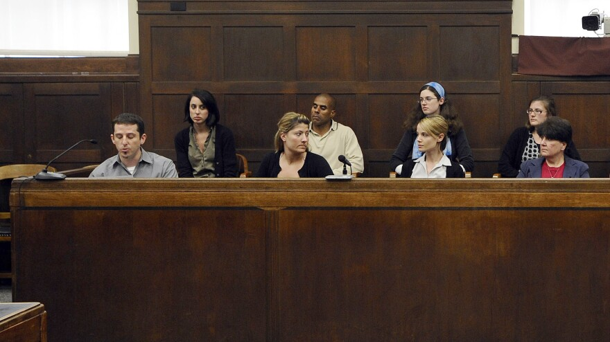 The jury sits in the jury box as foreman Michael Gregory (left) issues a statement in June 2009 after announcing a kidnapping conviction in Suffolk Superior Court in Boston.