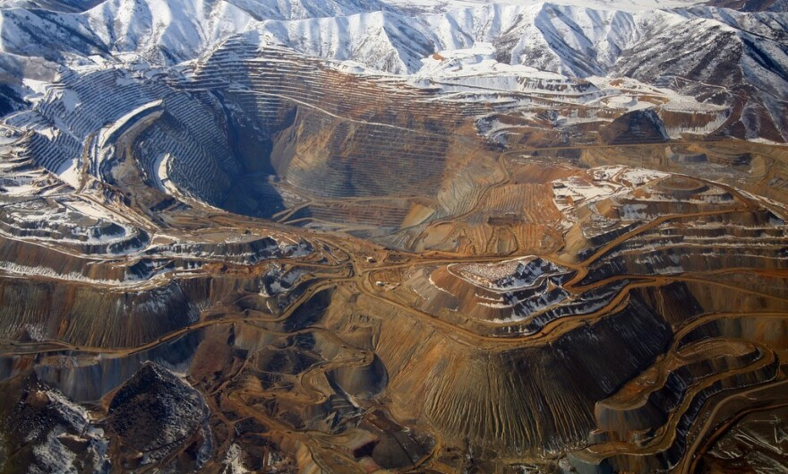 An aerial view of a large open-pit mine, ringed by snow capped mountains.