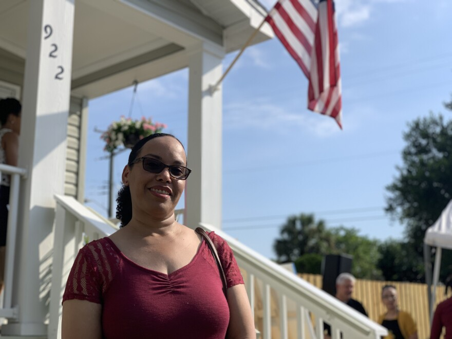 Helga Torres stands in front of the porch of her new modular home, built to be affordable and part of a new lease-to-purchase program