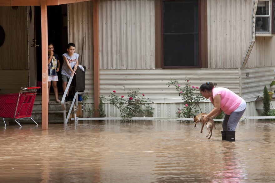 Alejandra Ventura lifts her dog out of the water after the Brazos River topped its banks and flooded a mobile home park in Richmond, Texas, on Tuesday.