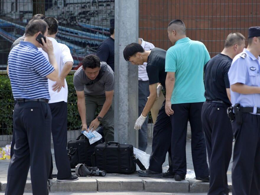 Chinese officials work near the site of a reported blast just south of the U.S. Embassy in Beijing, on Thursday.