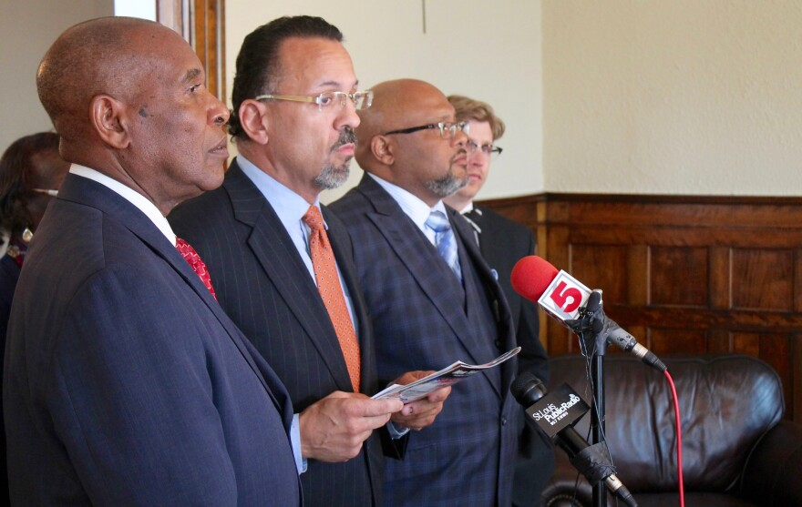 Normandy Mayor Patrick Green (center) speaks to the media during a news conference last year. Green says it doesn't make much sense to spread out Proposition P money based on population.