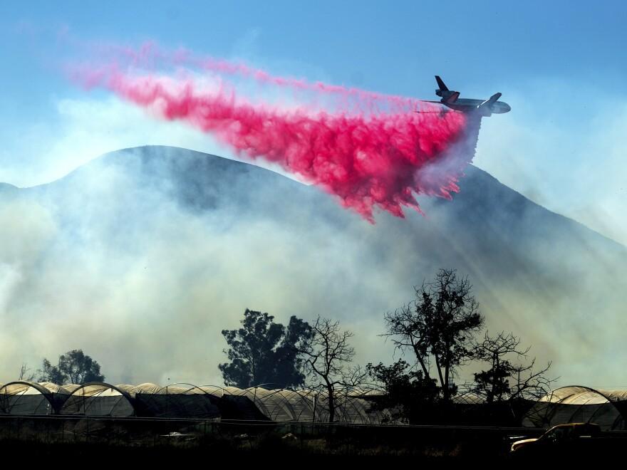 An air tanker drops retardant as the Maria Fire approaches Santa Paula, Calif., on Friday.