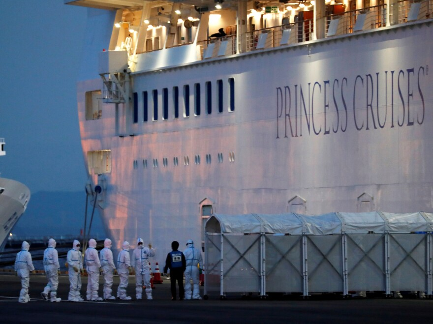 Officers wear protective gear as they work to remove people who tested positive for coronavirus from the cruise ship Diamond Princess. The ship is under quarantine at the Daikoku Pier Cruise Terminal in Yokohama, Japan.