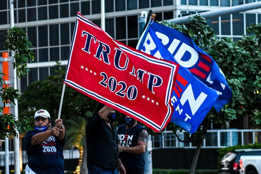 Supporters of US President Donald Trump and Democratic presidential nominee and former Vice President Joe Biden wave flags prior to Biden's arrival for an NBC townhall outside of the Perez Art Museum in Miami, Florida on October 5, 2020. (Chandan Khanna, AFP via Getty Images)