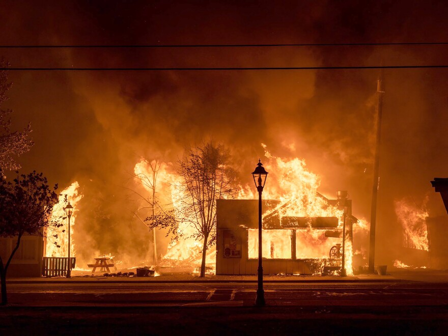 Buildings are engulfed in flames as a wildfire ravages Talent, Ore., on Sept. 8, 2020. Unfounded rumors that left-wing activists were behind the fires went viral on social media, thanks to amplification by conspiracy theorists and the platforms' own design.