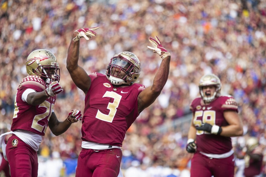 Three FSU football players celebrating a touchdown at Doak Campbell Stadium.