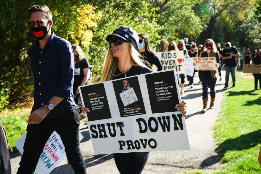 """Celebrity Paris Hilton carries a protest sign inscribed with the words """"Shut Down Provo."""""""