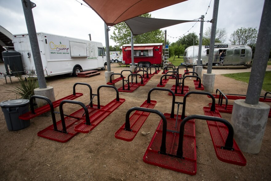 Tables at a food truck court have been turned over to prevent customers from eating on-site.