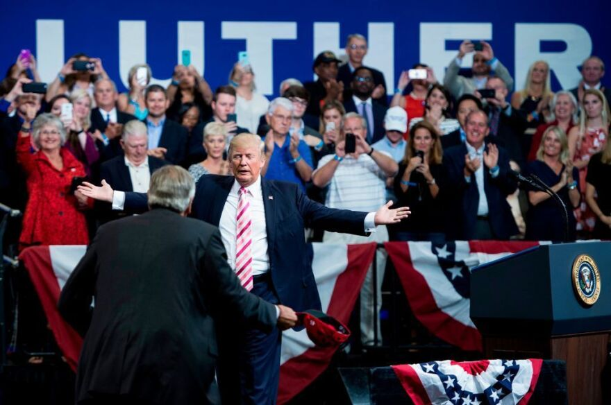 President Trump is greeted by Sen. Luther Strange on Friday in Huntsville, Ala.