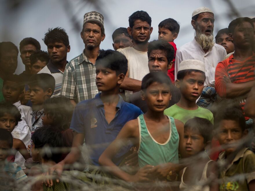 "Rohingya refugees gather in the ""no man's land"" behind Myanmar's barbed-wire-lined border in Maungdaw district, Rakhine state, in 2018. Some 700,000 refugees fled into Bangladesh following a brutal crackdown by the Myanmar military in 2017."