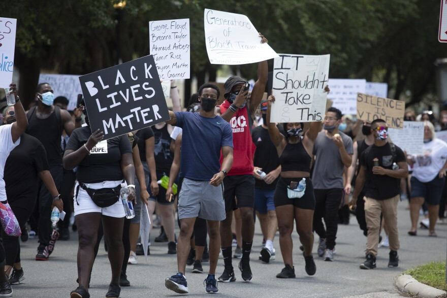 a group of protesters marches down a Tampa Park.
