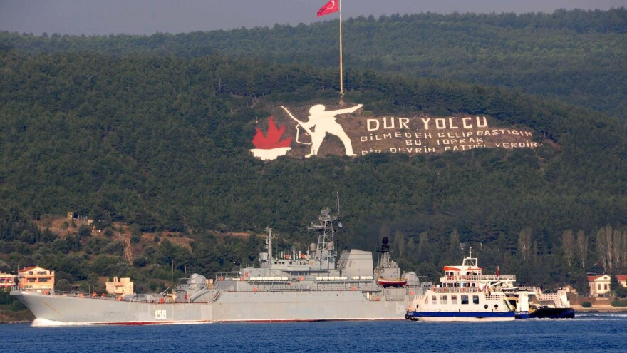 """The Russian naval ship Caesar Kunikov passes through the Dardanelles strait in Turkey to the Mediterranean Sea on Sunday. The memorial on the mountain commemorates the World War I Gallipoli campaign, with a sign citing a Turkish poem: """"Stop passenger. The land you come upon without knowing is the place an era had ceased."""" Russia began launching military operations in Syria last Wednesday."""
