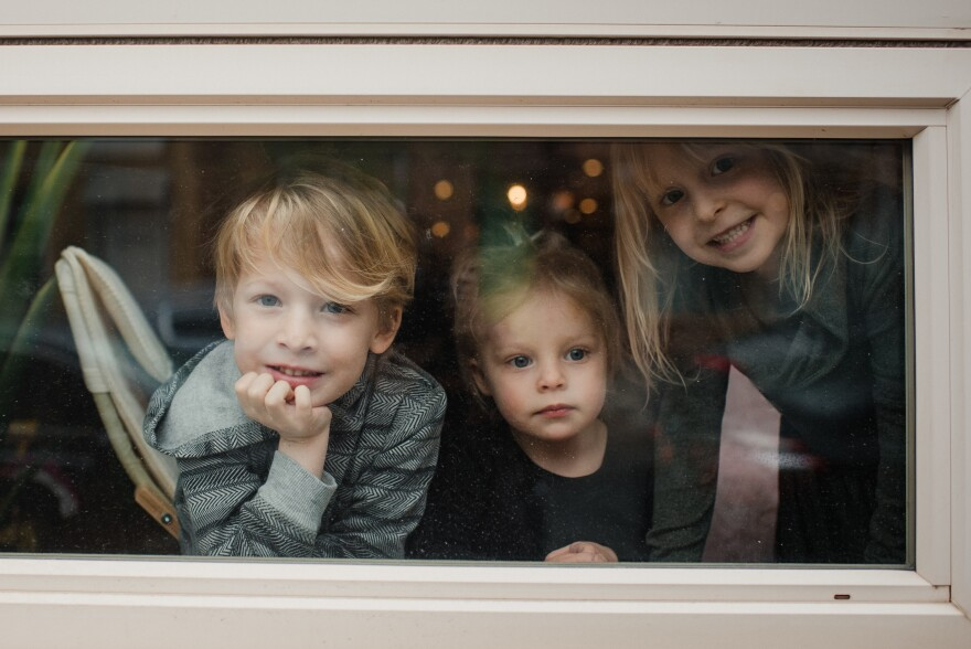 Matias McIntosh-Brix, 5, and his sisters Vivien, 2, and Nora, 5, play by the window at their home in Philadelphia on March 31. Parents Stacy Brix and Joel McIntosh both work in the health care industry and are alternating between their jobs and being at home with the kids.