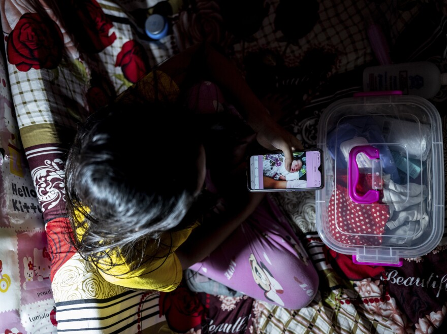 Jianne looks at a photo of her newborn son, whom she placed for adoption. The 21-year-old made the decision because she feared she could not provide for him during the pandemic. <em>July 10. </em><em>Nueva Vizcaya, Philippines.</em>