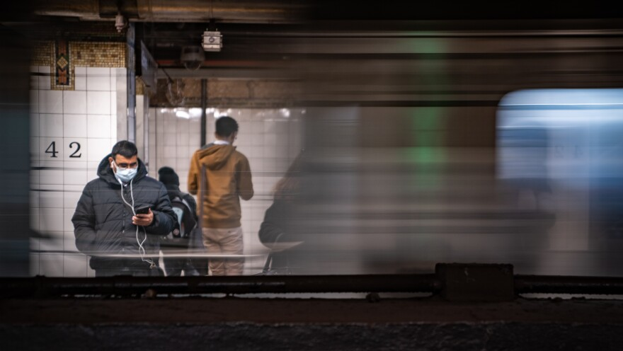 A commuter wearing a medical mask waits for a train Thursday at Grand Central Station in New York City. Several dozen cases have been confirmed in New York state, and the East Coast as a whole saw its first two confirmed deaths related to COVID-19, in Florida.