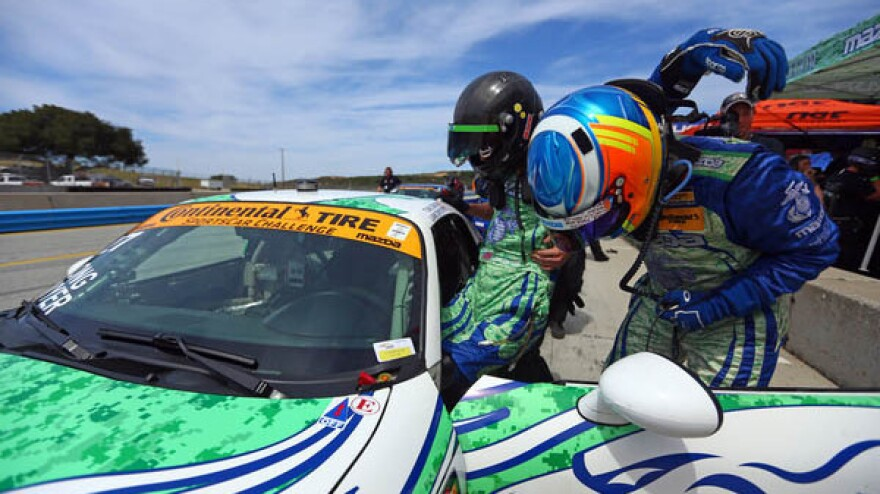 Liam Dwyer is assisted into the driver's seat of his racecar before his professional racing debut.