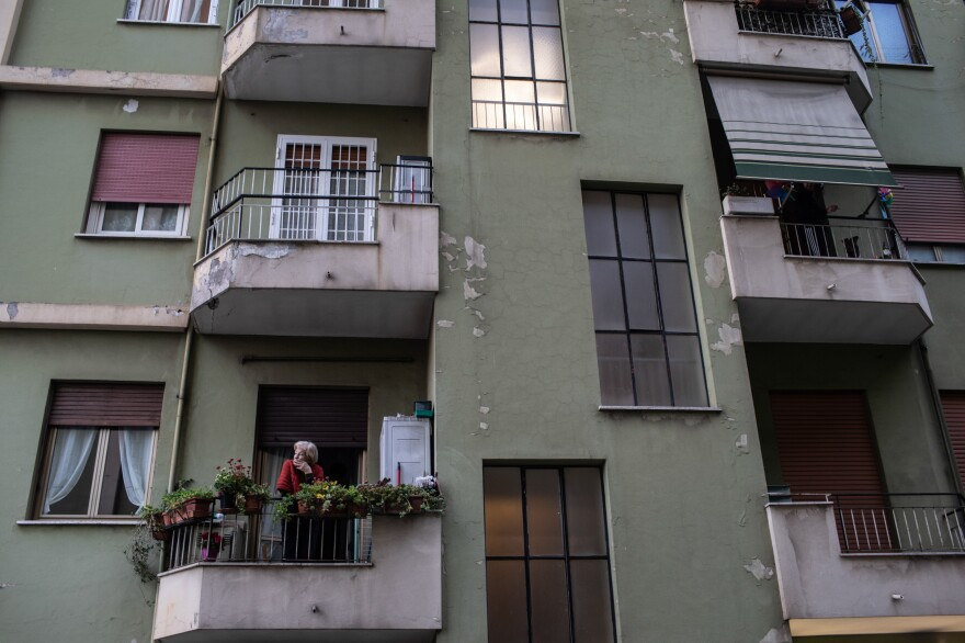 A woman looks out from her balcony in the Prenestina neighborhood of Rome.