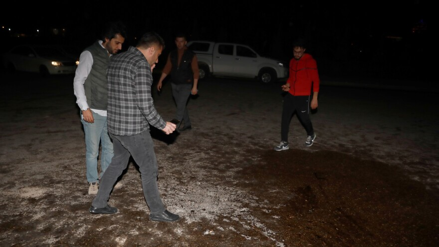 People inspect the area where one of the fired rockets was hit at Bahtiyari neighborhood on Monday in Erbil, Iraq.