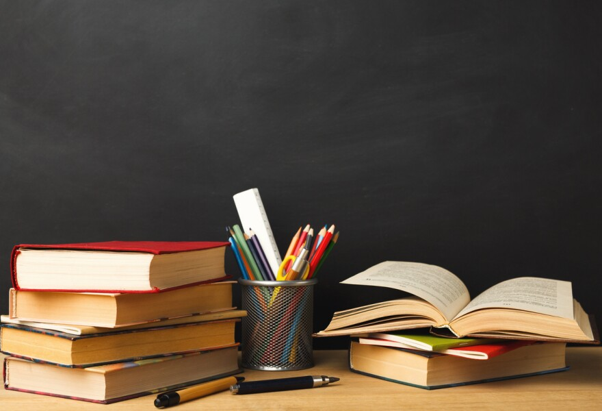 A photo of books and a cup of pens in front of a black board.