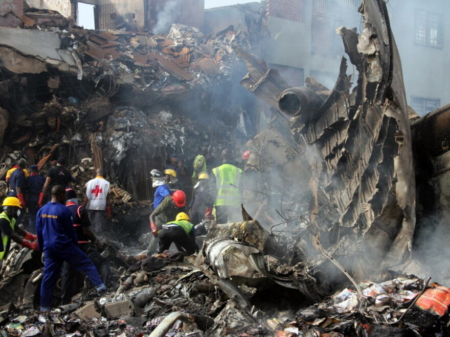 Monday, before a storm blew through, rescuers and firefighters searched through the crash site in Lagos.