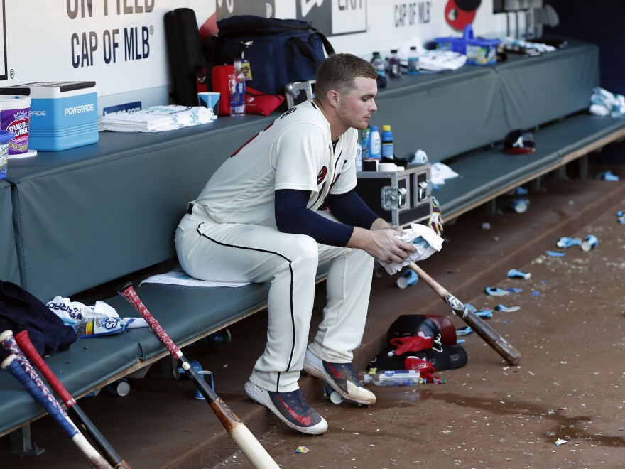 "Atlanta Braves pitcher Sean Newcomb takes a seat on the bench after losing his bid for a no-hitter in the ninth inning Sunday. Shortly after that home game against the Los Angeles Dodgers, the Braves released a statement calling Newcomb's old tweets ""hurtful and incredibly disappointing."""