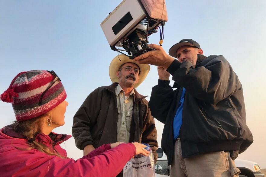 Kristy Bly, Randy Matchett and Kurt Kreiger inspect part of a drone at UL Bend National Wildlife Refuge in Montana.