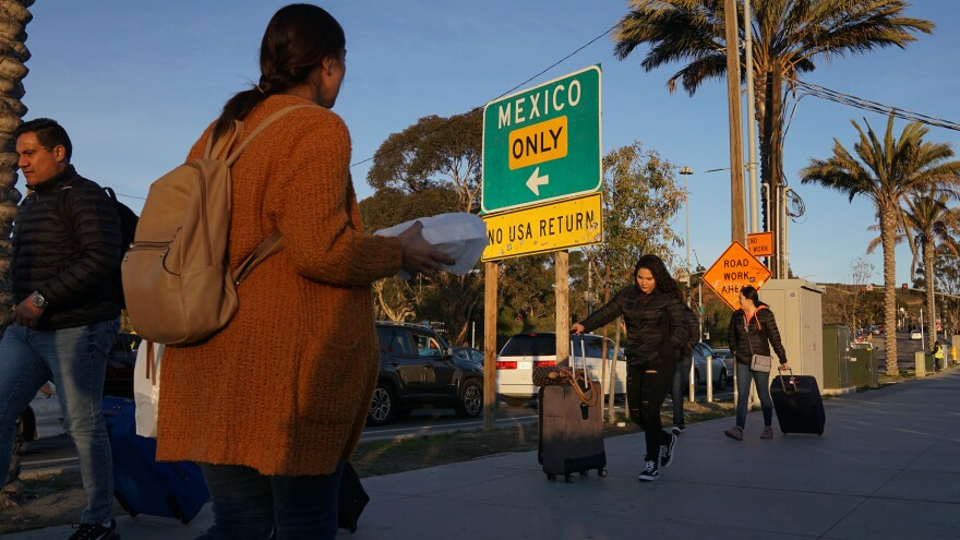 Shoppers walk toward the San Ysidro, Calif., Port of Entry after making purchases at outlet malls along the US-Mexico border on Dec. 29.