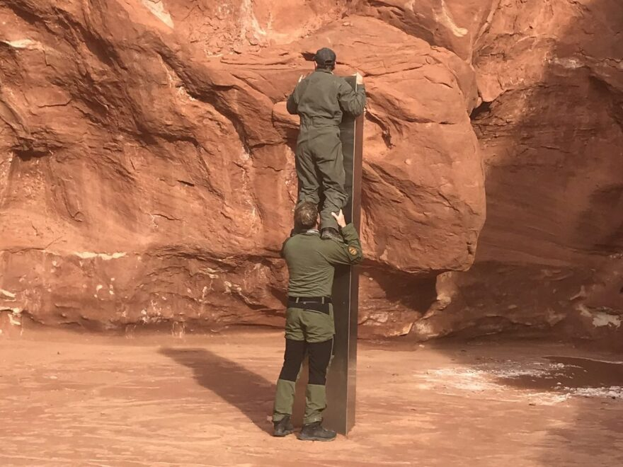 One man stands on the shoulders of another to peer on top of the monolith.