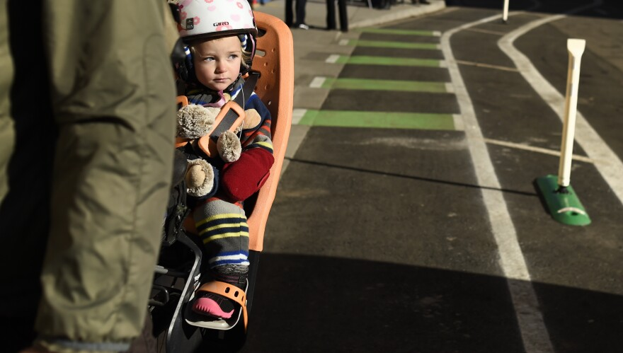 Maxine Parrish, 18 months old, is one of the youngest people to enjoy a new bike lane in Denver last month. Two avid bicyclists argue that better bike infrastructure allows slower cycling and a wider age-range of riders.