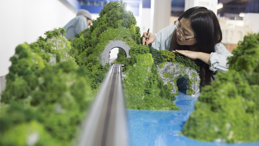Model maker Yu-ting Ling works on part of the Gulliver's Gate Asia display.