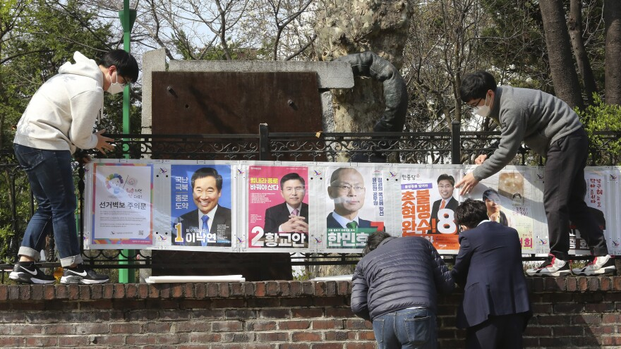 South Korean election officials put up posters of candidates in Seoul, South Korea, on April 2. The country will hold April 15 legislative elections on schedule, and the government's handling of the coronavirus pandemic is a major issue in the vote.