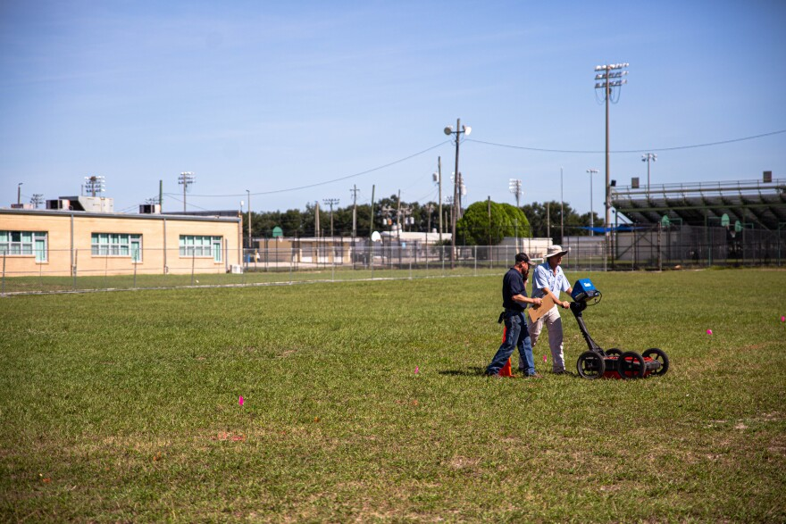 Two men on a field at King High School use a machine that resembles a lawn mower to use radar to locate coffins.
