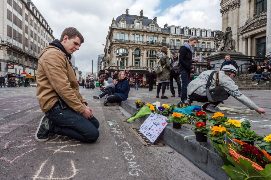 A man looks at flowers and messages of support outside the stock exchange in Brussels on Tuesday following the deadly attacks.