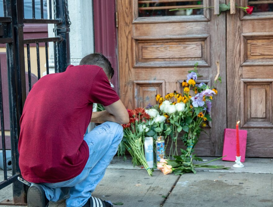 """A man kneels in front of a vigil for shooting victims in Dayton, Ohio, Aug. 5, 2019. This shooting was labeled a """"mass shooting"""" by the media, but shootings with similar number of victims are often ignored. This article attempts to understand the difference."""