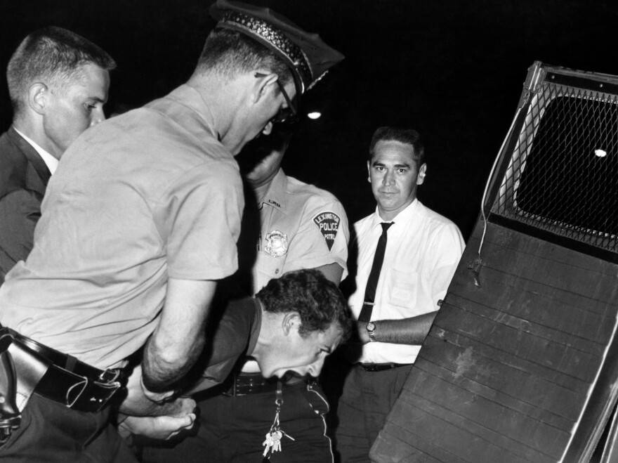A white heckler arrested during an anti-segregation demonstration in Lexington, Ky., is hustled into a police car in August 1963. Forty years later, the <em>Lexington Herald-Leader</em> ran a correction apologizing for the newspaper's lack of coverage of the civil rights movement.
