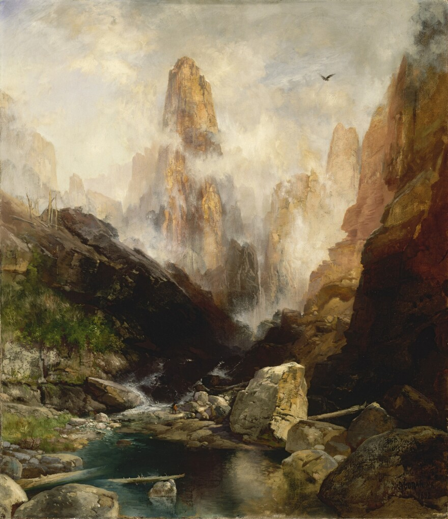 Landscape painting of a towering mountain with misty peaks and a river below. A man in red is dwarfed by mountain and rock.