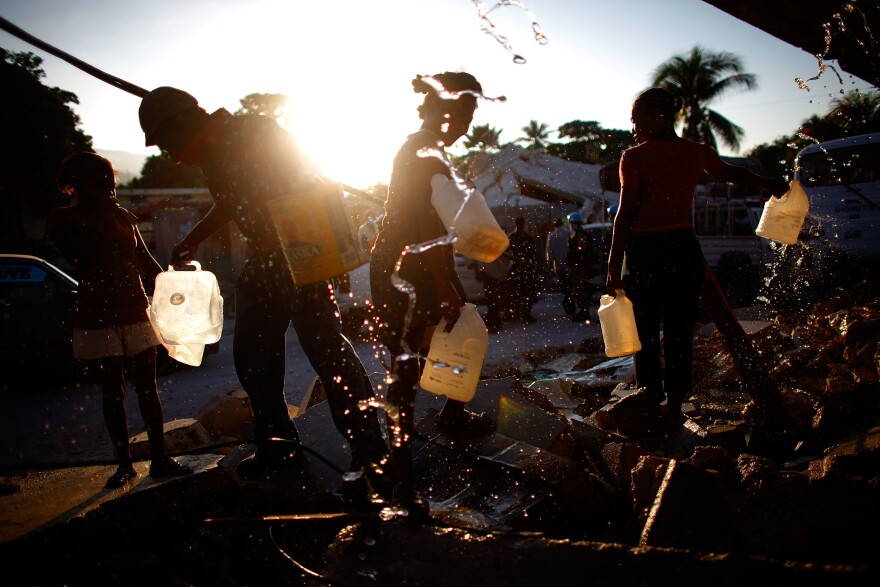 With fresh water in short supply, men and women gather around broken pipes to collect drinking water in Port-au-Prince in the days following the quake.