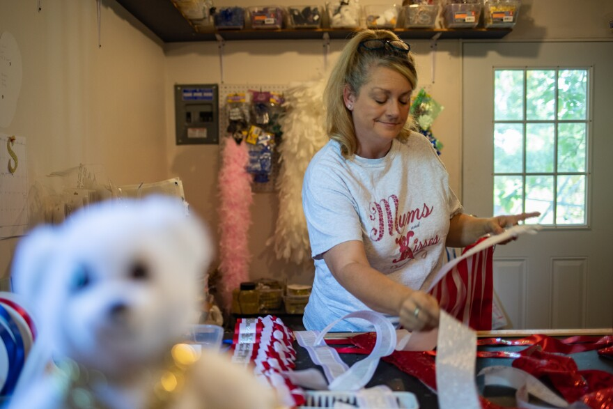 Shannon Gonzalez grabs a piece of ribbon while working on a mum.