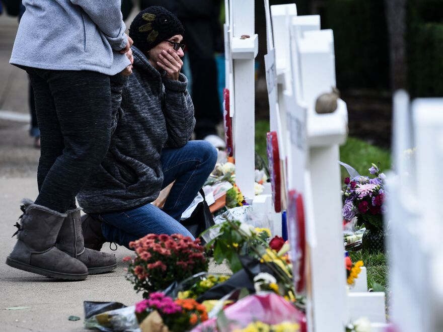 People pay their respects at a memorial outside the Tree of Life synagogue in Pittsburgh after a shooting there left 11 people dead. Many people see a connection between President Trump's anti-immigrant rhetoric and hate crimes.