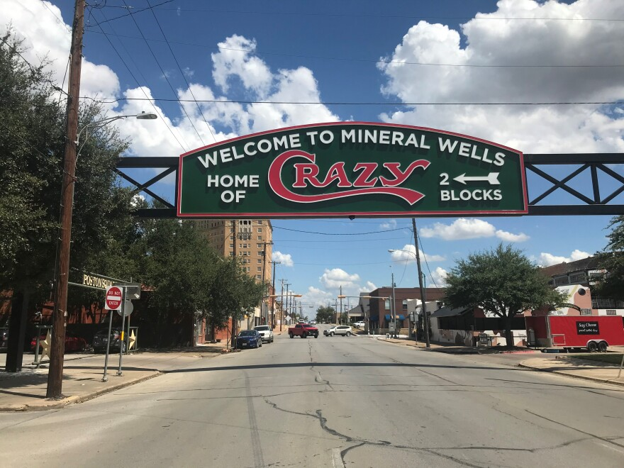 "In this picture, a large green sign above a downtown street welcomes people to Mineral Wells. It calls the city the ""Home of CRAZY."""
