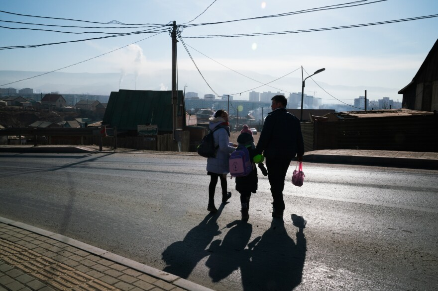 Oyutan lives with his family in Ulaanbaatar's <em>ger</em> district, an unplanned area on the capital city's outskirts where low-income migrants have settled. He escorts two of his daughters to school, wary of distracted drivers.