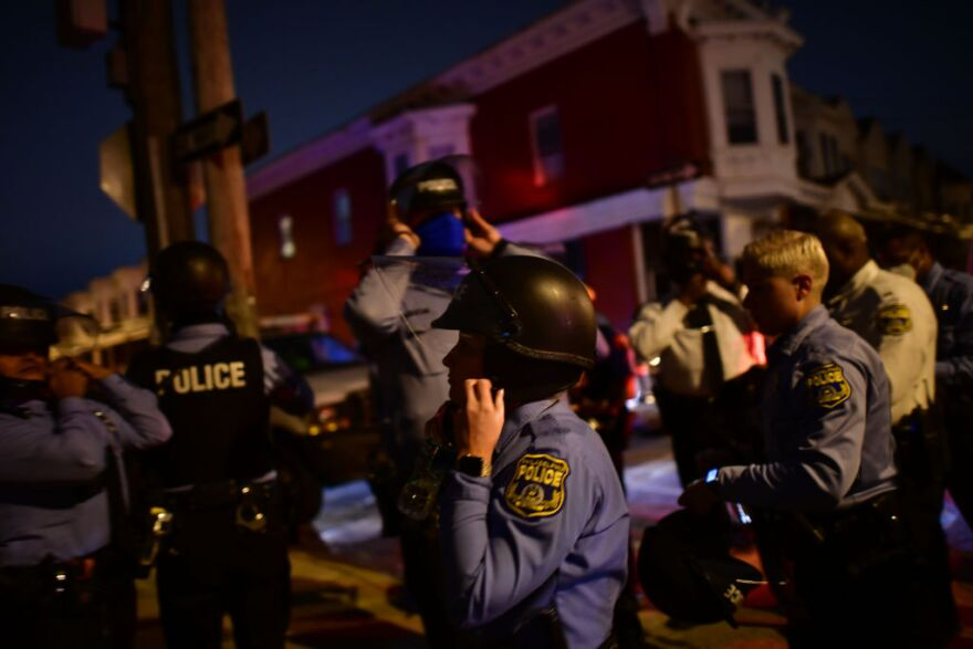 Police strap themselves into their tactical helmets before reinforcing a barricade line facing demonstrators near the location where Walter Wallace Jr. was killed by two police officers on October 27, 2020 in Philadelphia, Pennsylvania. (Mark Makela/Getty Images)